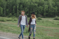 Couple holding hands while walking on roadside by field at forest