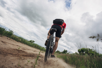 Low angle view of man riding mountain bike on dirt road against cloudy sky