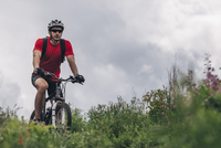 Determined man riding mountain bike against cloudy sky