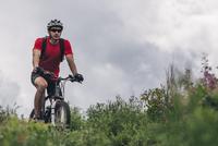 Determined man riding mountain bike against cloudy sky 11016034053| 写真素材・ストックフォト・画像・イラスト素材|アマナイメージズ