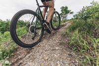 Low section of man riding mountain bike on dirt track 11016034054| 写真素材・ストックフォト・画像・イラスト素材|アマナイメージズ