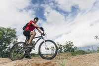 Low angle view of man riding mountain bike in rural setting against sky