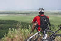 Rear view of man sitting by mountain bike on hill