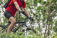 Low section of man with mountain bike in forest