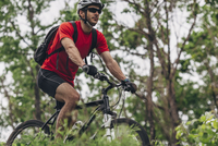Confident man riding mountain bike in forest