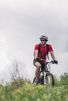 Confident man riding mountain bike against cloudy sky