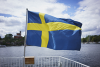 Swedish flag on railing by water against cloudy sky