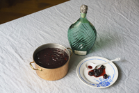 High angle view of blueberry syrup in pot with plate and bottle on tablecloth
