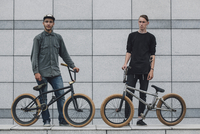 Confident friends standing with bicycles on sidewalk against wall