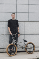 Teenager standing with bicycle against wall
