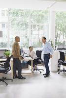 Happy businessmen communicating with female colleague at creative office 11016034249| 写真素材・ストックフォト・画像・イラスト素材|アマナイメージズ
