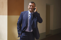 Confident businessman talking on mobile phone while standing at office