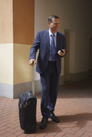 Happy businessman holding mobile phone and suitcase while standing at office