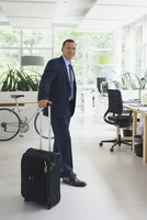 Confident businessman standing with suitcase at creative office