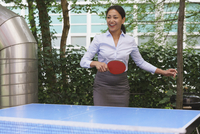 Confident businesswoman playing table tennis at creative office