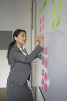 Businesswoman writing on adhesive note attached over whiteboard at creative office 11016034283| 写真素材・ストックフォト・画像・イラスト素材|アマナイメージズ