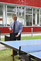 Happy businessman playing table tennis at creative office