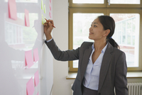 Businesswoman writing on adhesive note attached over whiteboard at office 11016034316| 写真素材・ストックフォト・画像・イラスト素材|アマナイメージズ