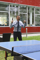 Happy businessman enjoying while playing table tennis at creative office 11016034319| 写真素材・ストックフォト・画像・イラスト素材|アマナイメージズ