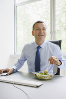 Smiling businessman having salad at desk in creative office