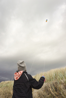 Rear view of boy flying kite against cloudy sky