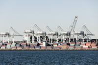 Cargo containers and cranes by sea against sky