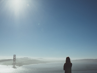Rear view of woman looking at broken bridge over sea against clear blue sky