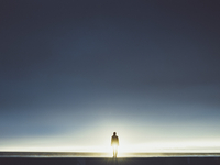 Silhouette man standing on seashore against clear sky during sunny day
