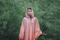 Young woman wearing raincoat standing amidst plants during rainy season 11016034453| 写真素材・ストックフォト・画像・イラスト素材|アマナイメージズ