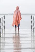 Rear view of woman wearing raincoat standing on jetty during rainy season 11016034454| 写真素材・ストックフォト・画像・イラスト素材|アマナイメージズ