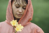 Close-up of beautiful woman wearing raincoat holding yellow flowers in rainy season