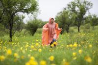 Woman wearing raincoat running amidst yellow flowering plants in rainy season 11016034458| 写真素材・ストックフォト・画像・イラスト素材|アマナイメージズ