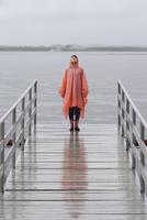 Woman wearing raincoat standing on jetty during rainy season 11016034459| 写真素材・ストックフォト・画像・イラスト素材|アマナイメージズ