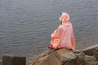 Thoughtful woman wearing raincoat sitting on rock at lakeshore during rainy season 11016034460| 写真素材・ストックフォト・画像・イラスト素材|アマナイメージズ