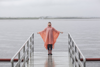 Woman wearing raincoat enjoying rainy season while standing on jetty 11016034462| 写真素材・ストックフォト・画像・イラスト素材|アマナイメージズ