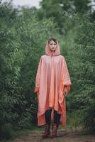 Portrait of woman wearing raincoat standing amidst plants during rainy season 11016034466| 写真素材・ストックフォト・画像・イラスト素材|アマナイメージズ