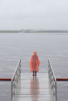 Rear view of woman wearing raincoat standing on jetty against clear sky 11016034467| 写真素材・ストックフォト・画像・イラスト素材|アマナイメージズ