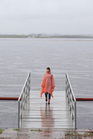 Woman wearing raincoat walking on jetty during rainy season 11016034469| 写真素材・ストックフォト・画像・イラスト素材|アマナイメージズ