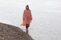 Woman wearing raincoat walking at lakeshore during rainy season 11016034470| 写真素材・ストックフォト・画像・イラスト素材|アマナイメージズ
