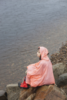 Thoughtful woman wearing raincoat sitting on rock at lakeshore in rainy season 11016034471| 写真素材・ストックフォト・画像・イラスト素材|アマナイメージズ