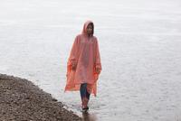 Woman wearing raincoat walking at lakeshore in rainy season 11016034474| 写真素材・ストックフォト・画像・イラスト素材|アマナイメージズ