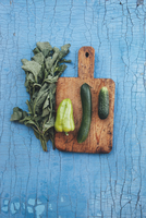 Directly above shot of fresh green vegetables with cutting board on wooden table