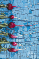 Directly above shot of red radishes arranged on blue wooden table