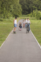 Siblings cycling on road amidst trees and grassy field at park