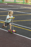Cute girl riding push scooter on playground