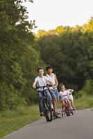 Siblings cycling on road against trees at park