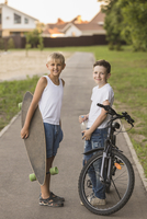 Smiling friends with skateboard and bicycle standing at park