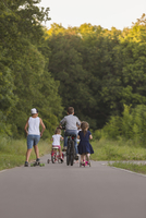 Rear view of siblings cycling on road against trees at park
