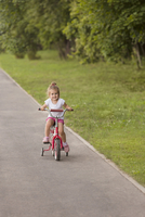Smiling cute girl cycling on road by grassy field at park