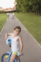 Portrait of girl with bicycle on road at park